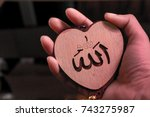 "Small photo of Muslim woman hand holding heart(Love) shaped tag written in Arabic ""Allah"" English meaning of God."