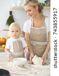 Small photo of Mother and little daughter are cooking in the kitchen. Spending time all together or happy family concept