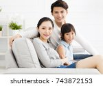 happy asian family on sofa in... | Shutterstock . vector #743872153