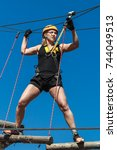 Small photo of young girl in a mountain helmet walks at a height on wooden logs with ropes in an alpinist adventure park against a blue sky. training mountaineers in the mountains. rope park. leisure in nature