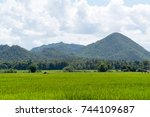 green field with mountain and... | Shutterstock . vector #744109687