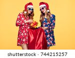 christmas. two young woman and... | Shutterstock . vector #744215257