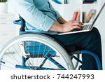 Small photo of Cropped shot of businessman sitting in wheelchair using laptop in office
