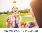 Small photo of The smile man juggle with apples near the woman outdoor