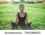 asian woman sitting on grass... | Shutterstock . vector #744288853