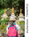 Small photo of Girl with backpack entering to buddhist temple in Wat Tham Seua (Tham Seua Temple) Krabi, Thailand.