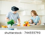 blonde girl is cooking with her ... | Shutterstock . vector #744555793