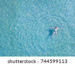 man swimming in turquoise water ... | Shutterstock . vector #744599113