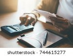 woman with bills and calculator.... | Shutterstock . vector #744615277
