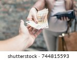 woman giving money to a man.... | Shutterstock . vector #744815593