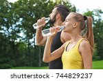 young sporty couple drinking... | Shutterstock . vector #744829237