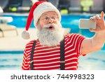 santa claus near the pool... | Shutterstock . vector #744998323