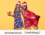 christmas. two young woman and... | Shutterstock . vector #744999667