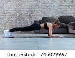 Small photo of Slim young brunette wearing black gym clothing doing abdominal bridge or front plank exercise in loft apartment.