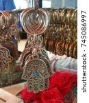 Small photo of A Closeup On A Silver Key Holder In The Shape Of Arabic Hamsa Talisman With The Hebrew Word Alive Printed On It