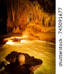 Small photo of White round stalagmite sitting on rock in underground cave pool at Marakoopa Caves in Tasmania