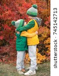 Small photo of Two brothers walking in the autumn Park.The older brother gently embracing his younger brother.