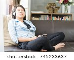 Small photo of Close up young asian woman short hair listening music from mobile phone by side the window in living room at home