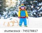 little boy enjoying a sleigh... | Shutterstock . vector #745278817