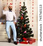 Small photo of Celebration and New Year mood concept. Santa Claus in red hat with cheerful face sends cheers. Man with beard and bow tie holds champagne glass. Guy near Christmas tree on wooden wall background