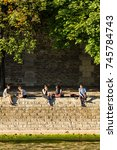Small photo of Paris, France - June 23, 2017: Embankment of the Seine River (Quai des Orfevres) in Paris at sunset. Parisians and tourists have picnic and relax on Cite Island.