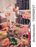 Small photo of X mas noel miracle, holy spirit! Close up cropped shot of gathered relatives, setted festive desktop with tasty treats plates, mealth of healthy food, arms putting sticks of sparklers together