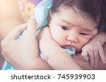 mother burping her newborn baby ... | Shutterstock . vector #745939903