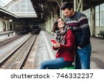 Small photo of Family couple being on platform, wait for train. Beautiful woman sits on suitcase, uses smart phone, looks at her lover, shows him photos. Young woman and man use cell phone on railway station