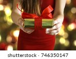 hands giving gold paper wrapped ... | Shutterstock . vector #746350147