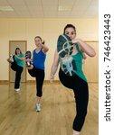 Small photo of women aerobic kick exercise at gym