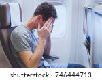 headache in the airplane  man... | Shutterstock . vector #746444713