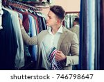 young guy deciding to buy on... | Shutterstock . vector #746798647