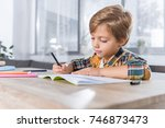concentrated little schoolboy... | Shutterstock . vector #746873473