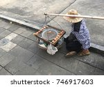 Small photo of The man sells grilled egg at footpath. Hawker/ peddler is one of career that you can see for general in any other places. It's a traditional sell style.