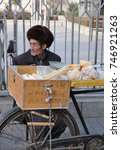 Small photo of In December 2012, Bread in wooden box on bicycle in front of an old Chinese man in brown shapka hat, Xian, Xaanxi province, China