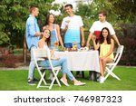 young friends having barbecue... | Shutterstock . vector #746987323