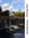 Small photo of MILFORD, CONNECTICUT - OCTOBER 2017: A waterfall with church in background in the center of Milford, Connecticut.