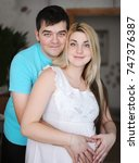Small photo of Happy man and his pregnant wife. Wife and husband. Parenthood and expecting baby. Vertical portrait