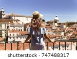 young woman looking at lisbon... | Shutterstock . vector #747488317