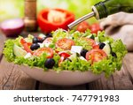 olive oil pouring into bowl of... | Shutterstock . vector #747791983