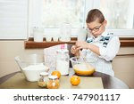 young boy whisking eggs... | Shutterstock . vector #747901117
