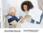 caring for a sick senior man in ... | Shutterstock . vector #747950107
