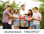 young friends having barbecue... | Shutterstock . vector #748139527