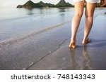 woman walking on the beach with ... | Shutterstock . vector #748143343