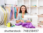 beautiful seamstress sewing at... | Shutterstock . vector #748158457