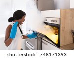 shocked woman looking at burnt... | Shutterstock . vector #748171393