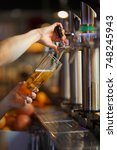 barman hands pouring a lager... | Shutterstock . vector #748245943