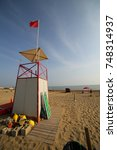 Small photo of watchtower for lifeguards on the sandy beach of the sea and the red flag