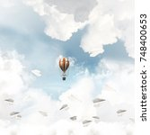 Small photo of Colorful aerostat flying among paper planes and over the blue cloudy sky. 3D rendering.