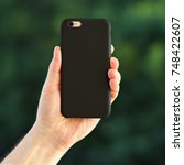 Small photo of Smart phone on the blurred background of the park in a black plastic case back view. Smart phone in man's hand. Template of phone case